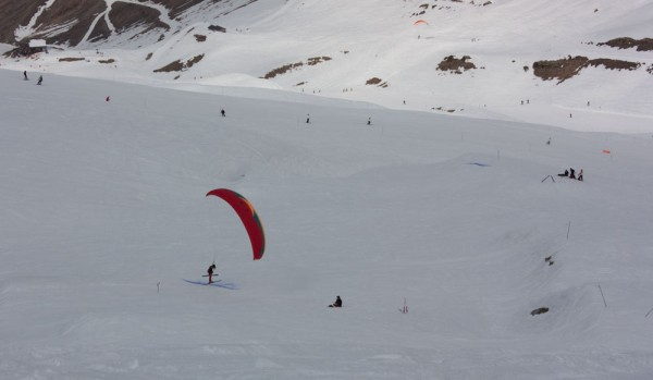 Anthony Green skis over a line in the snow, before getting airborne again and completing the course for good points. The glider on the right is flying along a line of sticks, kicking each one.